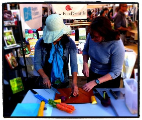 June Lee (left) tries her hand at cutting an onion like a chef after Kathleen Flinn's (right) demonstration.