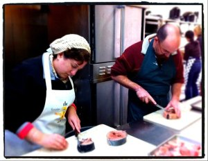 SFS board member, Patricia Eddy and her husband, John Eddy breaking down tuna steaks.